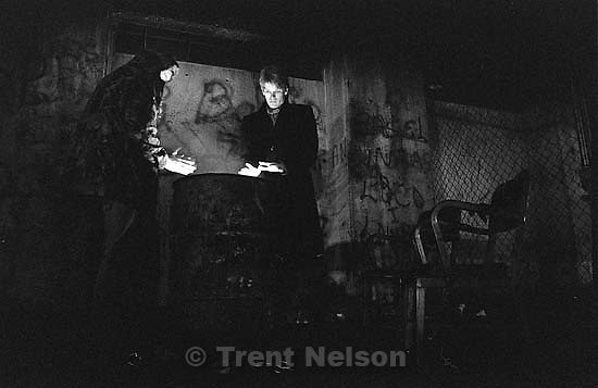 Trent Nelson and Alex Van Valin warming hands over a garbage can fire under the 4th south viaduct at night.<br />