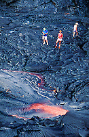 aerial of three visitors observing a lava pool.