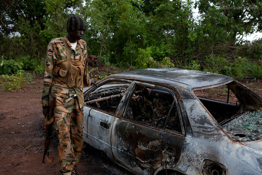 22 may 2010 - Western Equatoria State, South Sudan - An SPLA soldier inspects a car that was ambushed and burnt by the Lord's Resistance Army (LRA) on the road between Yambio and Tambura. The three victims were government officials in the State Ministry of Education: Mr. William Arkangelo Baabe, Mr. Gabriel Makana (49 years old) and Baraka Josefati (25 years old). The LRA has attacked a number of roads, villages, and clinics in the area over the last week pushing thousands of people to flee to larger towns for protection. Western Equatoria state has been rocked by LRA activities since 2006. Thousands of people have been forced from their homes as brutal attacks continue against the civilian population in the region and neighboring DRC and CAR. Photo credit: Benedicte Desrus