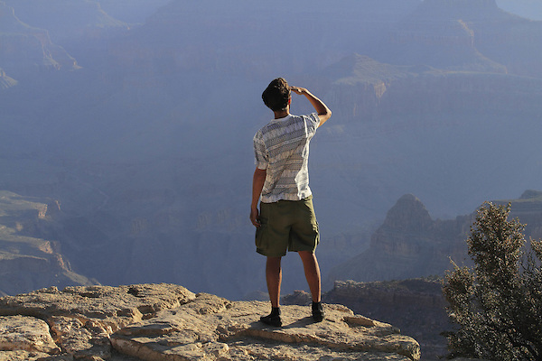 Man exploring the distance from the South Rim, Grand Canyon National Park, Arizona. . John offers private photo tours in Grand Canyon National Park and throughout Arizona, Utah and Colorado. Year-round.