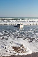 La embarcación es arrastrada hasta la playa por las olas
