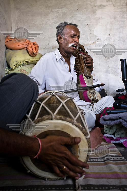 66 year old Manganiyar folk musician, Lakha Khan, plays the Sarangi (a short-necked stringed instrument) while his eldest son, Dane Khan (only hands visible) accompanies him on a Dholak (a small hand drum) at their home in Raneri Village.