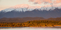 Coastal sunset in winter with Mount Adams of Southern Alps in background, Westland Tai Poutini National Park, UNESCO World Heritage Area, West Coast, New Zealand, NZ