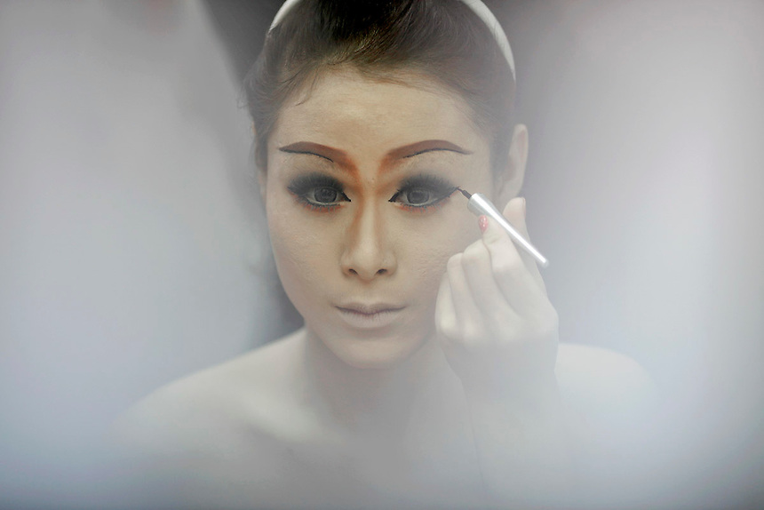A transvestite performer checks her make-up before going onto stage at the Tiffany's show in Pattaya late February 10, 2012. Originating as a one man show performed for friends on New Yearีs eve in 1974 in Pattaya, 150 km (90 miles) east of Bangkok Tiffany show became world famous transvestite cabaret with dozens of artists performing every night. Pattaya, a magnet for foreign tourists seeking sun, sea, watersports and racy nightlife, was a sleepy beach town until the 1970s and started to swell during the Vietnam War when U.S. troops, sailors and airmen flocked there for rest and relaxation.  Picture taken February 10, 2012. REUTERS/Damir Sagolj (THAILAND)