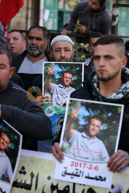 Palestinians hold posters bearing a portrait of Palestinian journalist Mohammed al-Qiq who is imprisoned in an Israeli jail during a protest in the West Bank city of Hebron, on February 10, 2017. Photo by Wisam Hashlamoun