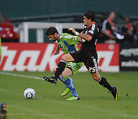 DC United forward Santino Quaranta (25) fights for possession of the ball against Seattle Sounders midfielder Pat Noonan (25).  Seattle Sounders. defeated DC United 1-0 at RFK Stadium, Thursday July 15, 2010.