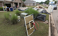 NWA Democrat-Gazette/DAVID GOTTSCHALK Interior housing materials, furniture, appliances and debris are stacked Tuesday, June 4, 2019, outside a residence on Turtle Bay Drive in Fort Smith. Homes in the neighborhood are beginning the process of recovering following flooding by the Arkansas River.