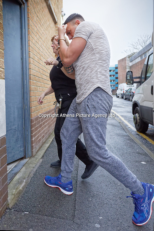 Pictured: Tom Carney (R) is escorted by a security officer into Swansea Magistrates Court, Wales, UK. Monday 18 February 2019<br /> Re: Tom Carney, 27, from Swansea, has been charged with murder after the death of  76-year-old David Phillips in the Cimla area of Neath, in Wales, UK.<br /> Phillips was found dead at a propertyat about 9.15am on Thursday (14 Feb 2019) morning after reports of a disturbance.