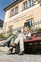 Germany, Thuringia, Ilmenau: woman sitting on a bench beside Goethe statue in front of Goethe-City-Museum | Deutschland, Thueringen, Goethe- und Universitaetsstadt Ilmenau: Frau sitzt auf einer Bank neben Goethestatue vor dem Goethe-Stadt-Museum