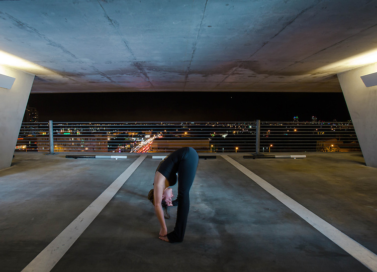Young Woman holding yoga poses in a public space