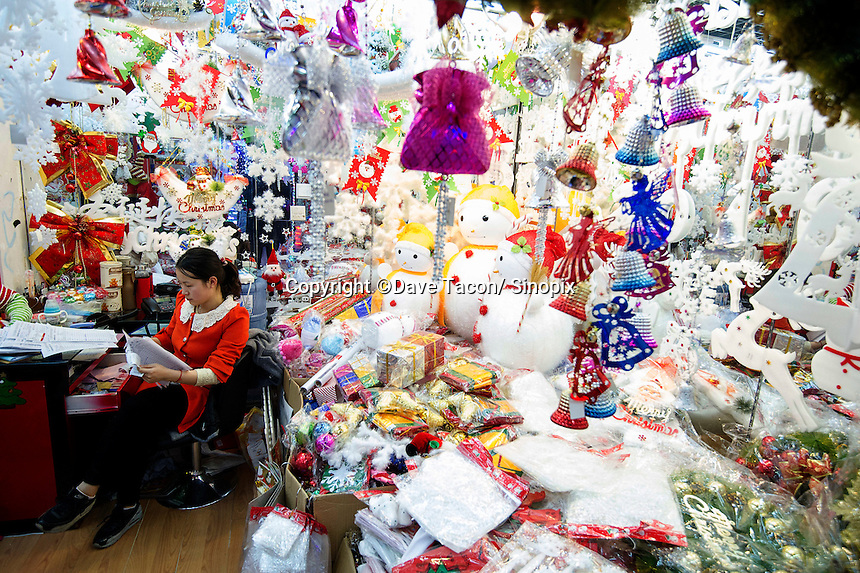 November 27, 2015, Yiwu China - A vendor sits behind a desk in a stall of Christmas decorations inside the Festival Arts section of the Yiwu International Trade Market. Yiwu International Trade Market is the world's largest whole sale market for small commodities. Christmas decorations are available for bulk purchase all the year round.Photo by Dave Tacon / Sinopix
