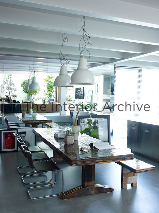Designer chairs by Mies van der Rohe line the dining table with a bench by Piet Hein Eek in the dining area of the loft. The industrial pendant light fixtures are by Piero Lissoni for Boffi. The photographs leaning against the mirrored wall are by Bruce LaBruce, far left, and Steven Klein, right