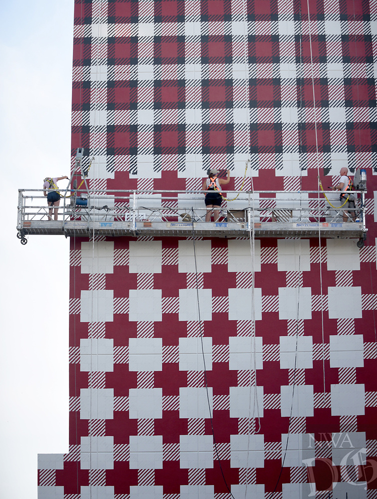NWA Democrat-Gazette/DAVID GOTTSCHALK Maggie Boll (from left), Jessica Nedberg and Justin Olson, with Olson Paint Studios of Indianapolis, Ind., paint Wednesday, August 7. 2019, a plaid pattern on the south side of the new Graduate Fayetteville hotel. In March, The Graduate Fayetteville's new owners Chicago-based AJ Capital Partners said the renovated hotel is expected to open in the fall in time for Razorback football. The Fayetteville location will join AJ Capital's other boutique Graduate Hotels located in university-anchored cities around the U.S.