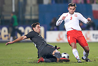 Clint Dempsey of the USA tackles the ball away from Grzegorz Bronowicki of Poland. The United States defeated Poland 3-0 during an international friendly at Wisla Stadium in Krakow, Poland on March 26, 2008.