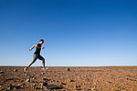 Running across the desert landscape of the Moon Plain, near Coober Pedy.  The lunar-like plain has been the setting for movies including Mad Max, Priscilla Queen of the Desert, and The Red Planet.  Coober Pedy, South Australia, AUSTRALIA.