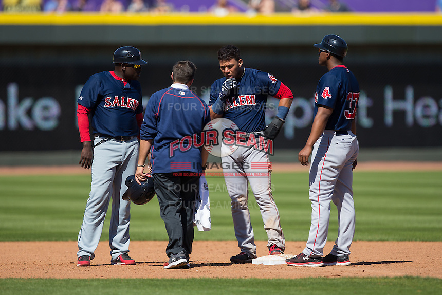 Yoan Moncada (center) is checked out by the trainer, coach Nelson Paulino (left), and teammate Carlos Mesa (37) after being hit in the face with a throw as he stole second base during the game against the Winston-Salem Dash at BB&T Ballpark on April 17, 2016 in Winston-Salem, North Carolina.  The Red Sox defeated the Dash 3-1.  (Brian Westerholt/Four Seam Images)