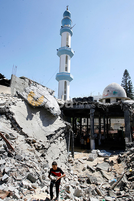 A Palestinian boy searches in the rubble of the heavily damaged al-Faruq mosque which was destroyed by Israeli strikes during the summer's fierce offensive, in Rafah in the southern Gaza Strip September 21, 2014. Photo by Abed Rahim Khatib