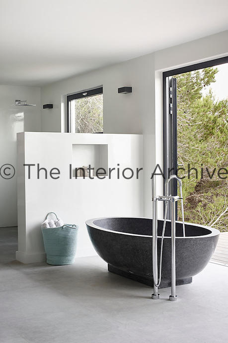 This wonderful bathroom belongs to the master bedroom, and boasts a huge double shower as well as a bath and sink that echo the organic shape of the outside tub. The pale bluish tones of the accessories provide a visual link to the sea and sky outside.