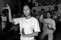 Children of Bassac. After stretching, Sophea rehearses the traditionnal Khmer moves. The articulation must be streched while the dancers are young. Legs, wrists, elbows, fingers, each part of the body is made more supple until  getting un-naturel moves. Phnom Penh, Cambodia - 2005
