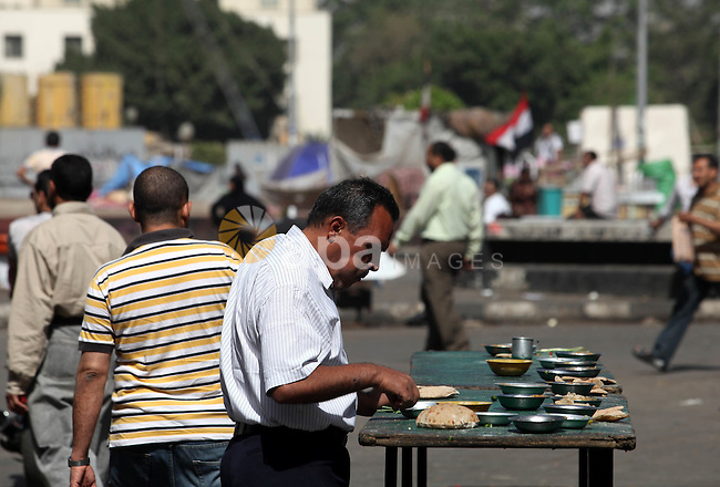 An Egyptian deals breakfast in Cairo's landmark Tahrir Square on June 3, 2012 after a night of protests. Hundreds of demonstrators are occupying Tahrir Square after a court sentenced ousted president Hosni Mubarak and his interior minister Habib al-Adly to life in prison but acquitted six security chiefs in the deaths of protesters last year. Photo by Majdi Fathi