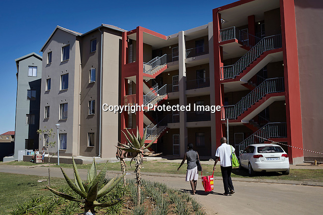 SOWETO, SOUTH AFRICA MAY 4: A couple walks outside the apartment block where they live on May 4, 2013 in Jabulani, section of Soweto, South Africa. Jabulani flats is one of the first apartment building developments in Soweto and local residents are just beginning learn how to live in an apartment. The residents of Soweto has seen massive investment such as shopping malls, parks, outdoor gyms in the township. Soweto today is a mix of old housing and newly constructed townhouses. The population in Soweto is estimated to be around one million people. A new hungry black middle-class is growing steadily. Many residents work in Johannesburg but the last years many shopping malls have been built, and people are starting to spend their money in Soweto (Photo by: Per-Anders Pettersson)