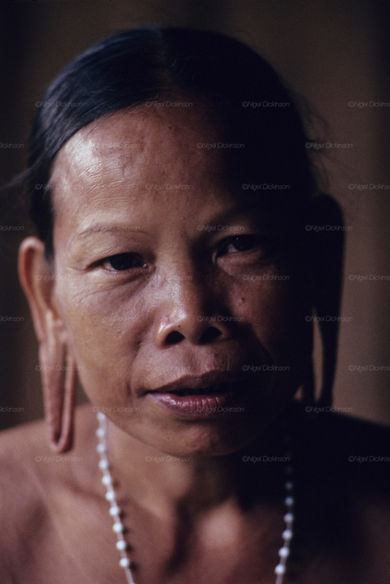 1991: Kenyah native woman, Gin, with distended earlobes, elongated to wear traditional earrings. Long Geng, Belaga district, Sarawak, Borneo. <br /> <br /> Tropical rainforest and one of the world's richest, oldest eco-systems, flora and fauna, under threat from development, logging and deforestation. Home to indigenous Dayak native tribal peoples, farming by slash and burn cultivation, fishing and hunting wild boar. Home to the Penan, traditional nomadic hunter-gatherers, of whom only one thousand survive, eating roots, and hunting wild animals with blowpipes. Animists, Christians, they still practice traditional medicine from herbs and plants. Native people have mounted protests and blockades against logging concessions, many have been arrested and imprisoned.