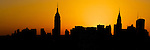 A silhouette of the midtown Manhattan skyline at sunset.  The Empire State Building and Chrystler building are clearly defined in this panoramic photo of New York City.