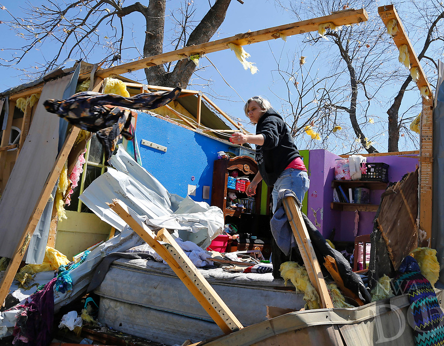 Jamie Mull salvages an article of clothing from a friend's tornado-damaged mobile home in Sand Springs, Okla., Thursday, March 26, 2015. (AP Photo/Sue Ogrocki)
