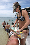 "Memorial Day weekend celebrants Jenniger Brannon, top, from Ocala and Latrill Gilbert, from Jacksonville Beach enjoy a little sun, water, and a ""margararita sandwich at the White Trash Bash at Dog Island off the coast of Carrabelle Sunday May 27, 2007.    (Mark Wallheiser/TallahasseeStock.com)"