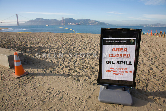A beach closed sign warns of contaminated water at Crissy Field while a container ship in the distance enters the San Francisco Bay (11/12/07). On November 7, 2007 the Cosco Busan container ship spilled an estimated 58,000 gallons of bunker fuel into San Francisco Bay after striking a tower of the San Francisco-Oakland Bay Bridge.