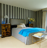Chinese-style cabinets flank the double bed in a bedroom with striped wallpaper and natural flooring