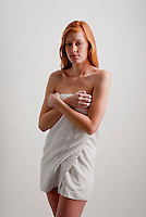 Young red haired woman wrapped in a towel