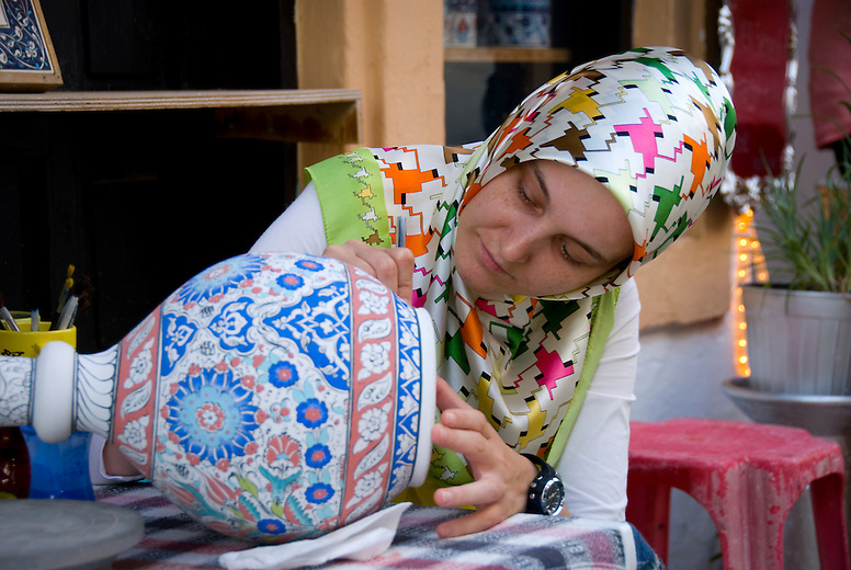 A woman producing Iznik (white clay) pottery, named for the town in western Turkey where the style originated. Though the tradition of pottery making was traditionally passed from father to son, excluding females, today many women take part in pottery craftsmanship.