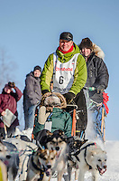 Linwood Fiedler and team run past spectators and down the Cordova Street hill with an Iditarider in the basket and a handler during the Anchorage, Alaska ceremonial start on Saturday March 4th during the 2017 Iditarod race. Photo ©2017 by Daniel Lent/SchultzPhoto.com