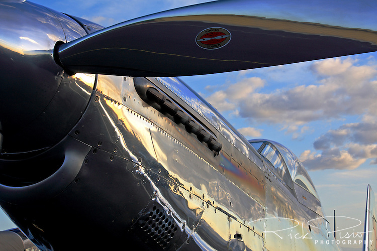 Clouds reflect off the highly polished fuselage of a North American P-51D Mustang