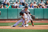 Zach Houchins (5) of the Salt Lake Bees slides into third base asTrent Woodward (8) of the Fresno Grizzlies tries to field the throw at Smith's Ballpark on September 4, 2017 in Salt Lake City, Utah. Fresno defeated Salt Lake 9-7. (Stephen Smith/Four Seam Images)