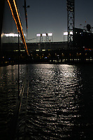 Field lights from what was then SBC Park, now AT&T Park, reflect in the waters of China Basin and the windows of a yacht on the bay.