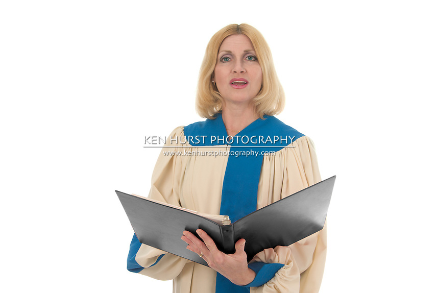 Blond woman in a choir robe holding a music notebook and singing.