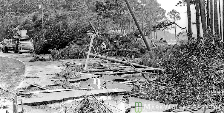 Photograph of power crews repairing the damage along US 98 near Eastpoint after Hurricane Elena churned in the Gulf of Mexico off the coast of the Florida panhandle in September 2, 1985.  Elena was the first major hurricane of the 1985 season and it's unusual path included a loop and went back and fourth along the Florida panhandle as a category 3 storm heavily damaging the Apalachicola, FL oyster industry.  Apalachicola recorded the highest surge and rainfall totals and whatever oyster industry wasn't ruined by Elena was finished off when Hurricane Kate followed  in November of the same season.