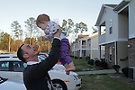Justin Griffith, a sergeant in the US Army, an atheist and a father, raises his 1-year-old daughter Zoe Griffith in the air at home in Fayetteville, NC, on Sunday, March 11, 2012.  Recently named as Military Director of American Atheists, Justin Griffith is trying to get atheists more respect within the military and has organized a pro-atheism event, Rock Beyond Belief, at Fort Bragg, where he is stationed.  Photo by Ted Richardson