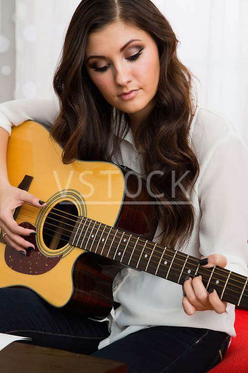Female composer playing guitar