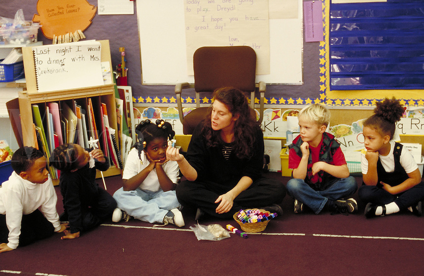 STUDENTS LISTENING CAREFULLY TO TEACHER AS THEY ALL SIT ON THE FLOOR. ELEMENTARY STUDENTS. OAKLAND CALIFORNIA USA CARL MUNCK ELEMENTARY SCHOOL.
