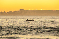 2  fishermen in a small boat with cray pots at dawn. Kaikoura Coast New Zealand.