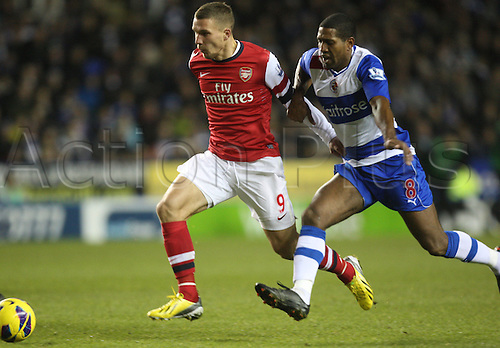 17.12.2012. Reading, England. ..Lukas Podolski of Arsenal and Mikele Leigertwood of Reading..in action during the Premier League match between Reading and Arsenal from Madejski Stadium