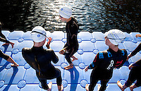 30 JUN 2011 - LONDON, GBR - Competitors wait on the pontoon for the start of the women's super sprint elimination round at the GE Canary Wharf Triathlon (PHOTO (C) NIGEL FARROW)