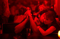 Patrons of the Mundo Bizarro bar in Buenos Aires' Palermo neighborhood enjoy drinks and conversation under dim red lights. In the wake of a disastrous nightclub fire that temporarily closed all the discos in the city, bars are seeing a lot of action. (Kevin Moloney for the New York Times)