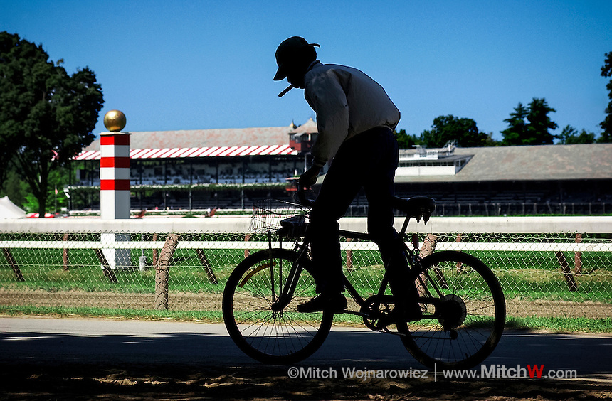 ©Mitch Wojnarowicz Photographer.Saratoga Springs NY Backstretch worker rides a bike back to a stable at the thoroughbred horse racing track here.20030823.Not a royalty free image. COPYRIGHT PROTECTED.www.mitchw.com.www.mitchwblog.com.518 843 0414_Mitchw@nycap.rr.com.ANY USE REQUIRES A WRITTEN LICENSE.NO Model release for this image