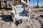 A tattered easy chair and sneakers abandoned in the flooded neighborhood of Bombay Beach, California