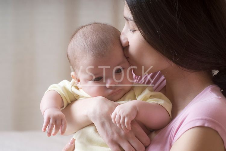 Mother kissing baby (6-11 months)
