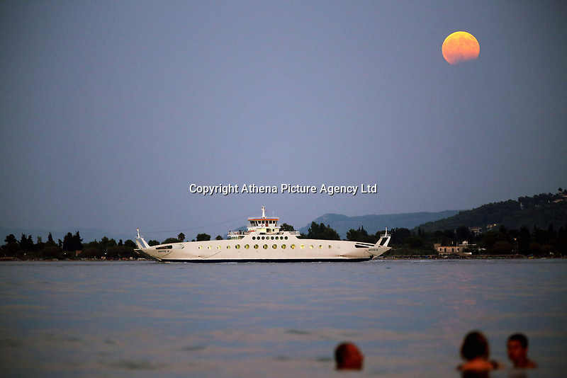 A full moon with a partial eclipse rises, while a ferry boat departs for Eretria and  people cool off in the sea in Oropos in the Evia Bay, 30 miles east of Athens, Greece. Monday 07 August 2017